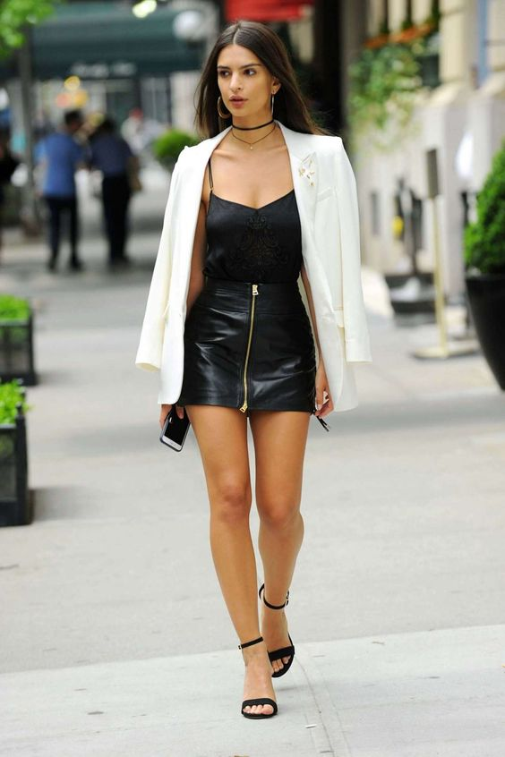 Emily Ratajkowski wearing a night out look with a black top, a black leather mini, a white blazer and black shoes