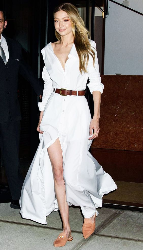 Gigi Hadid wearing a white maxi shirtdress with long sleeves, a brown belt and orange mules