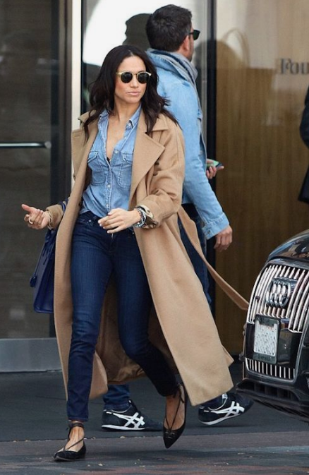 Meghan Markle wearing a chambray shirt, navy skinnies, black lace up flats and a camel coat for a spring look