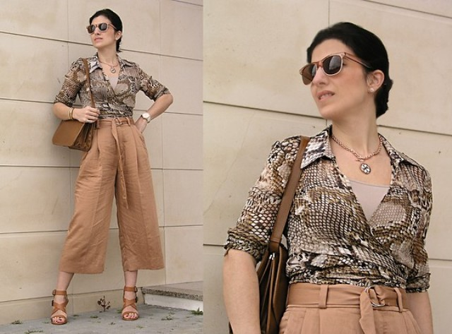 With beige top, light brown belted culottes, brown leather bag and brown lace up sandals