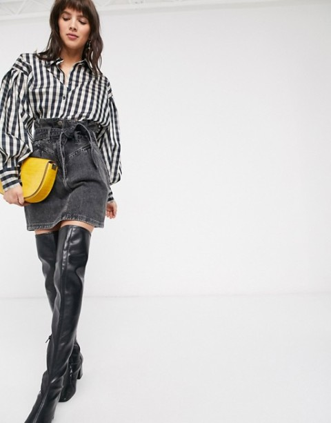 With black and white checked button down shirt, yellow bag and black leather over the knee boots