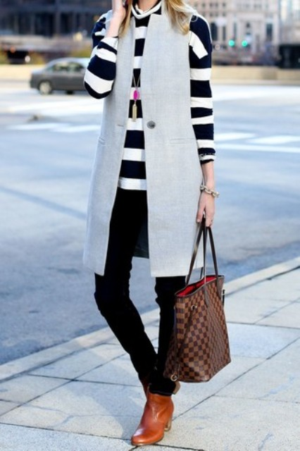 With black and white striped shirt, gray long vest, black trousers and brown leather ankle boots