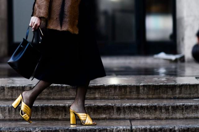 With black midi skirt, black tote bag and fur jacket