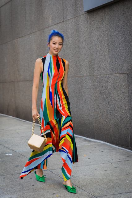 With colorful sleeveless maxi dress and golden bag