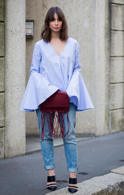 With cuffed jeans, black high heels and marsala leather fringe clutch