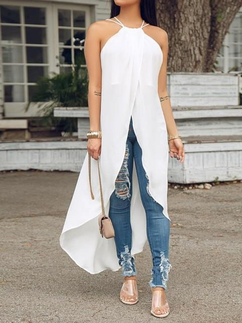 With distressed jeans, white long top and transparent shoes