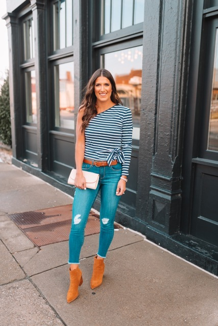 With distressed skinny jeans, brown belt, beige clutch and brown suede ankle boots