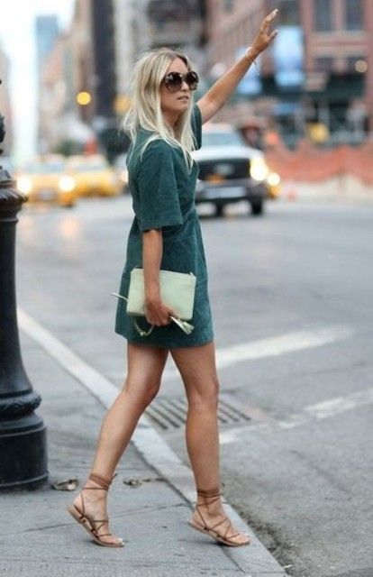 With emerald mini dress and lace up flat sandals