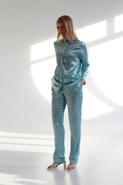 With light blue satin button down shirt and white low heeled sandals