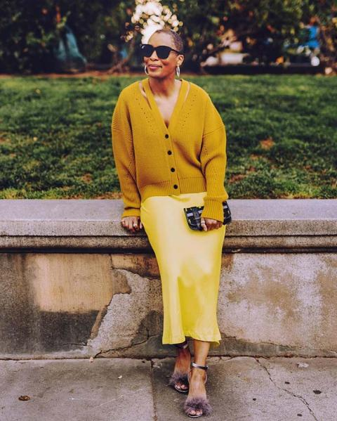 With mustard yellow cardigan, clutch and faux fur sandals