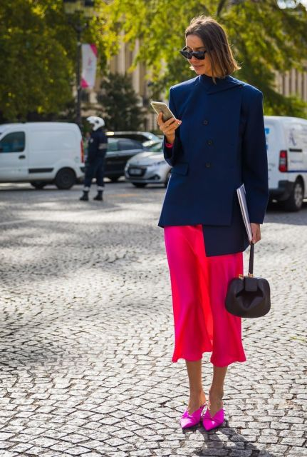 With navy blue asymmetrical blazer, black bag and red midi skirt