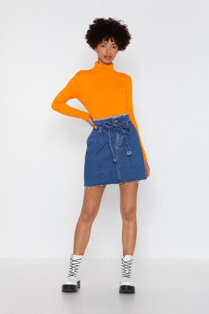 With orange turtleneck and black and white lace up ankle boots