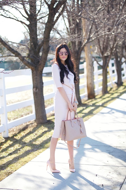With pale pink belted knee-length dress and pale pink pumps