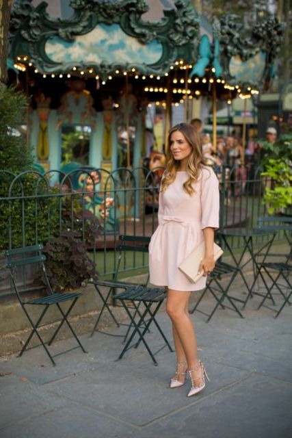 With pale pink mini dress and embellished high heels