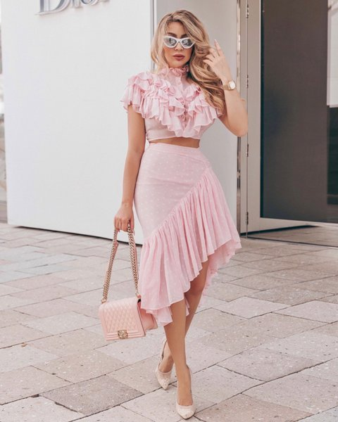 With pale pink ruffled crop shirt, ruffled asymmetrical skirt and beige pumps