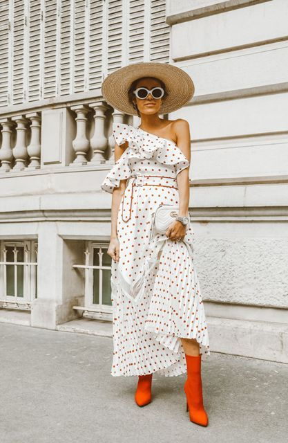With red mid calf boots, wide brim hat and white clutch