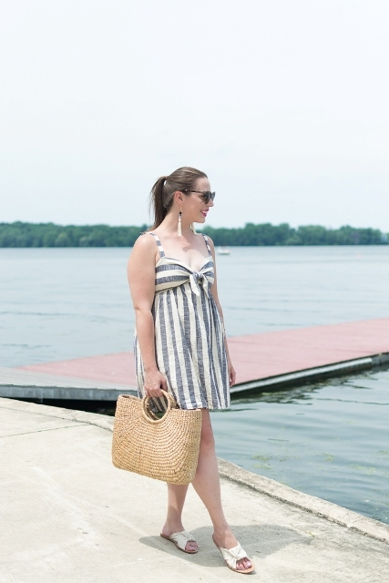 With straw tote bag and beige flat sandals