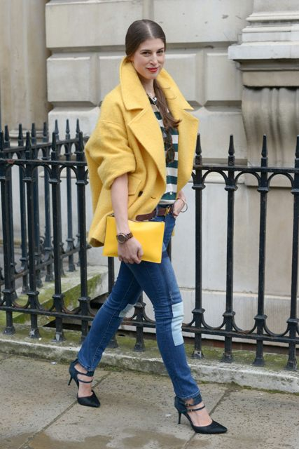 With striped shirt, light yellow jacket, skinny jeans and black shoes