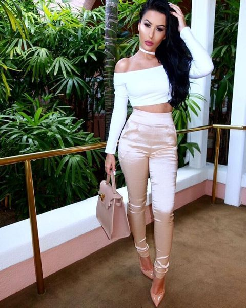 With white off the shoulder crop top, beige bag and beige patent leather pumps