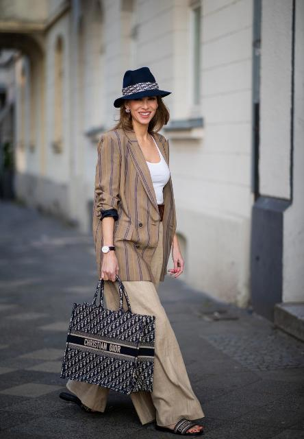 With white top, beige palazzo pants, flat sandals, striped loose blazer and hat