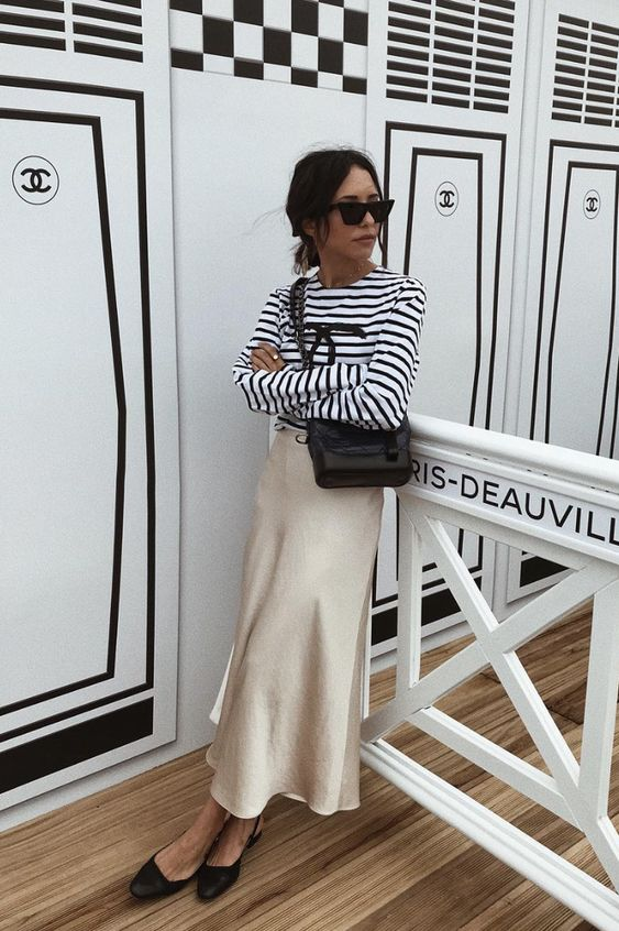 a Breton striped top, a champagne-colored midi slip skirt, black slingbacks and a black bag