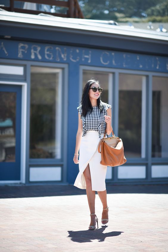 a black and white gingham top with ruffles, a white wrap midi skirt, white heels and a brown bag