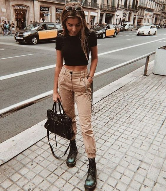 a black crop top, tan cargo pants, black combat boots and a black bag for a simple and stylish look