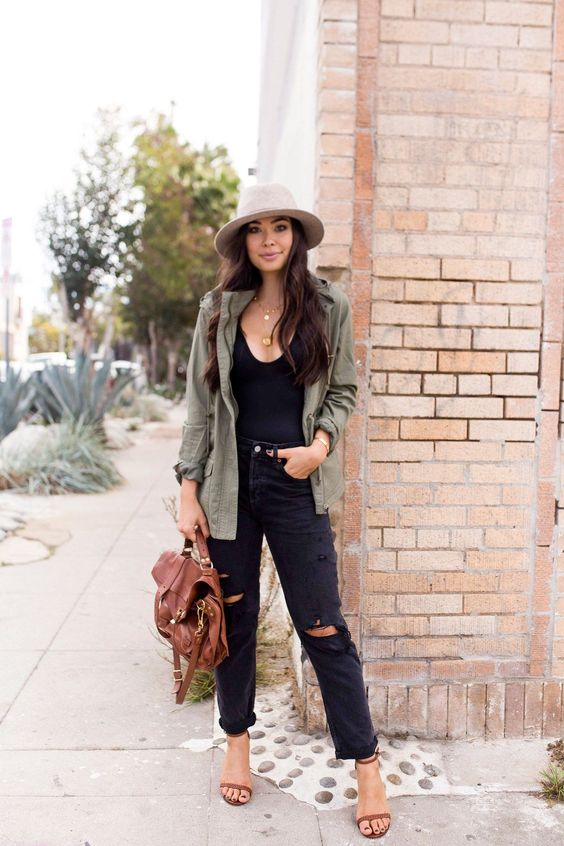 a black deep neckline, black ripped jeans, tan shoes, a green army jacket, a brown bag and a neutral hat
