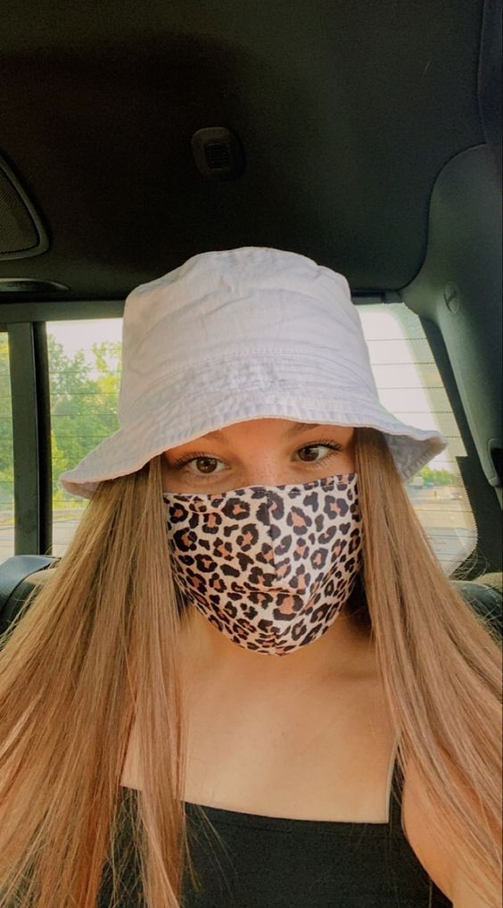 a black top, a white bucket hat and a leopard print face mask for a bold accent in the look