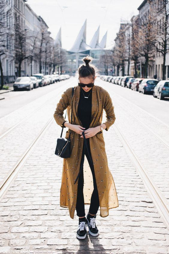 a black top, black skinnies, black Vans shoes, a black bag and a mustard printed duster
