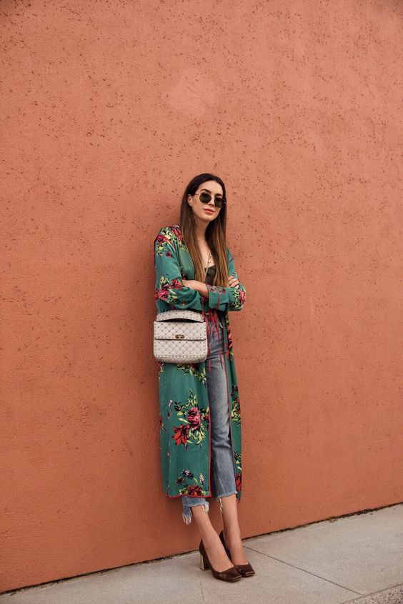 a black top, blue cropped jeans, brown heels, a green floral kimono and a neutral bag