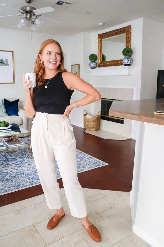 a black top, neutral trousers, brown mules and a necklace for an effortless summer work look