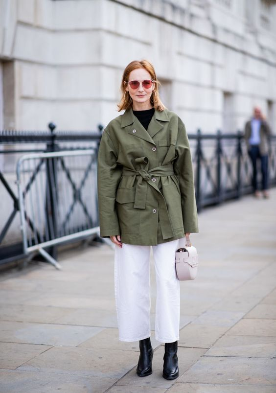 a black top, white wideleg trousers, black boots, a green safari jacket and a pale pink bag