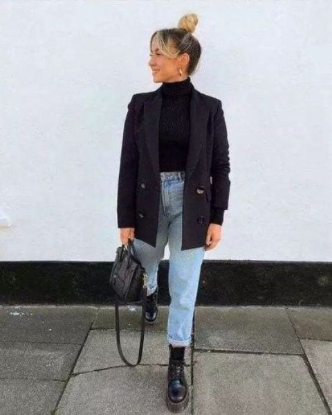 a black turtleneck, a black oversized blazer, light blue jeans, black combat boots and a black bag
