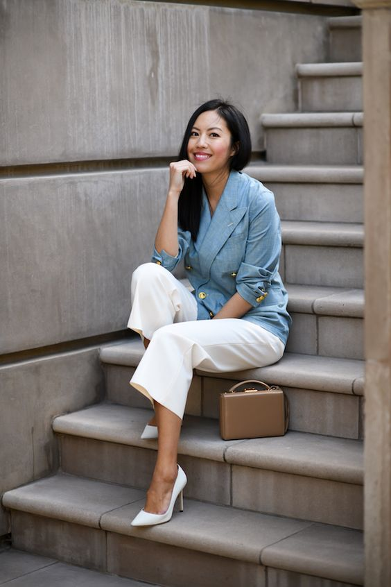 a blue linen blazer with gold buttons, creamy cropped trousers, white heels, a small tan bag