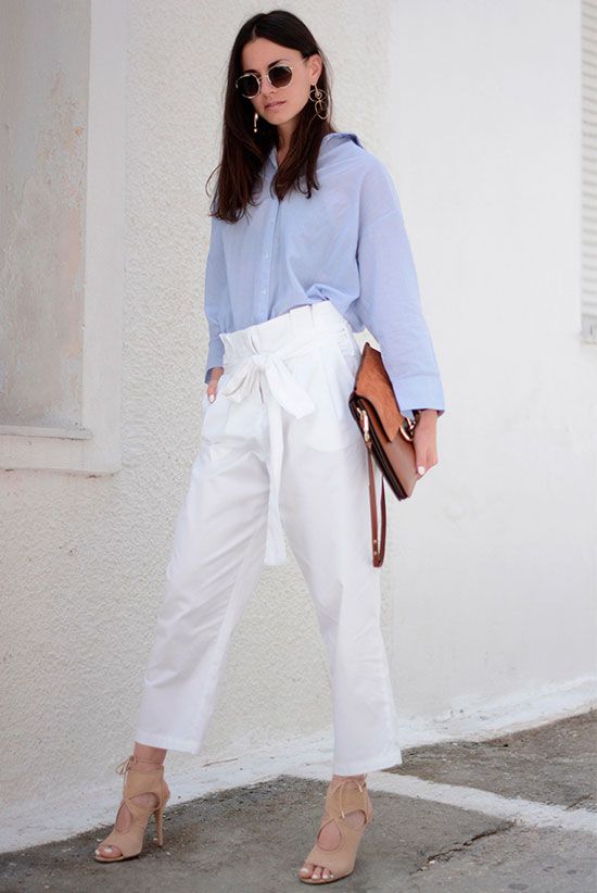 a blue oversized shirt, white paperbag pants, nude laser cut shoes, a brown clutch and statement earrings