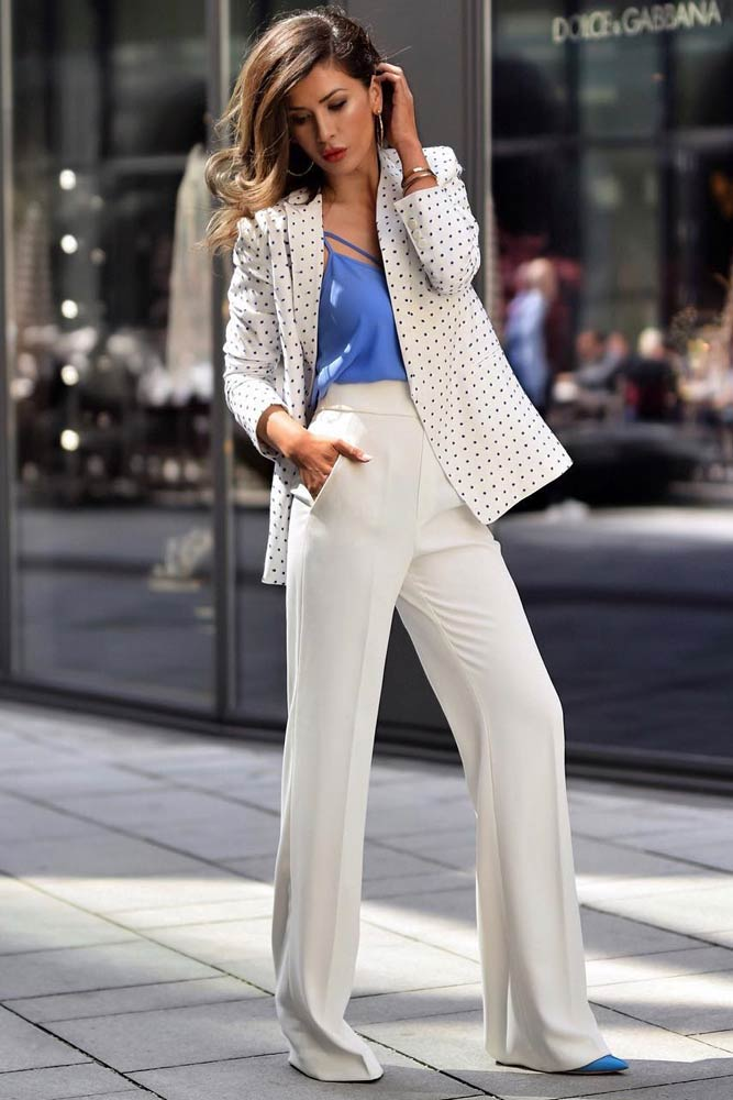 a blue strap top, creamy pants, a white polka dot blazer, blue heels and statement accessories
