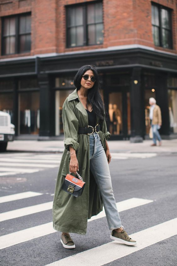 a casual look with a black top, blue jeans, green sneakers, a green duster with a belt and a two tone bag