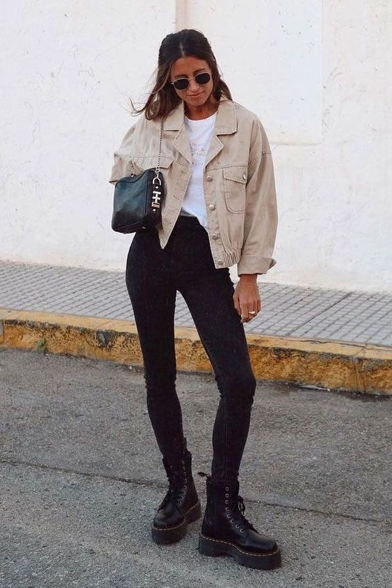 a casual look with black skinnies, black boots, a white tee, a tan denim jacket and a black mini bag