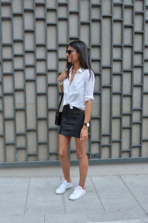 a casual outfit with a white shirt, a black leather mini, white sneakers and a black bag is stylish and simple