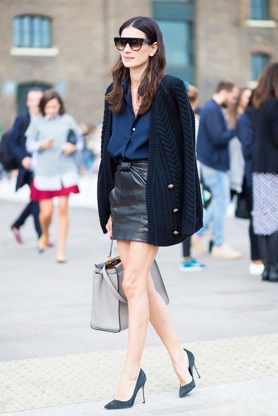 a fashionable work outfit with a navy shirt, a black draped leather mini, a knit cardigan, teal shoes and a grey bag