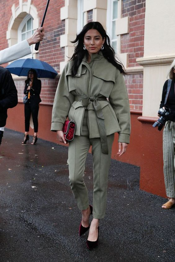 a green belted safari jacket, matching trousers, burgundy velvet shoes and a red clutch for a very chic look