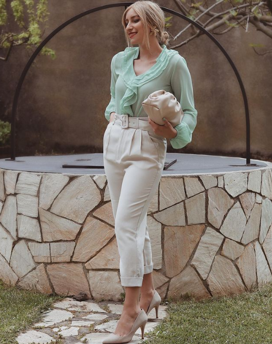 a green ruffle blouse, creamy trousers, nude shoes, a creamy bag and floral earrings