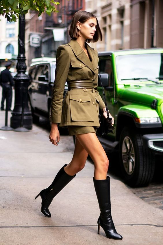 a green safari jacket and a matching mini skirt, knee boots and a black bag for a refined look