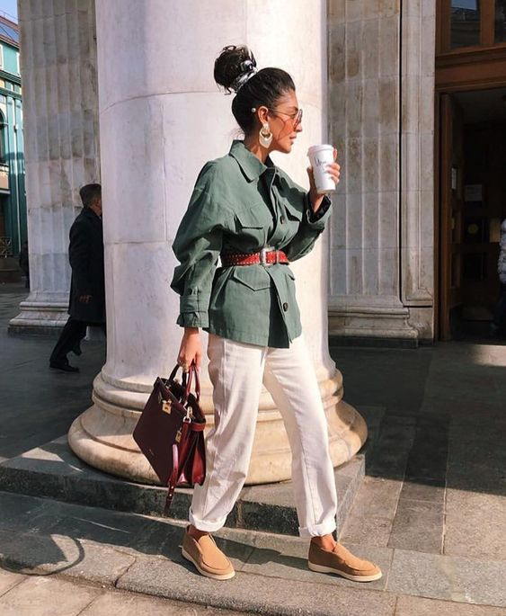 a green safari jacket, white trousers, brown moccasins, a red belt and a red bag look amazing together