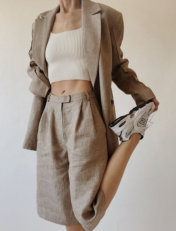 a grey linen shorts suit with an oversized blazer, bermuda shorts, a white crop top and neutral trainers