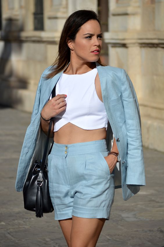a light blue short suit with a white crop top and fitting shorts and a blazer plus a black bag