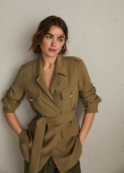 a long green safari jacket, green trousers and gold earrings for a stylish and chic look