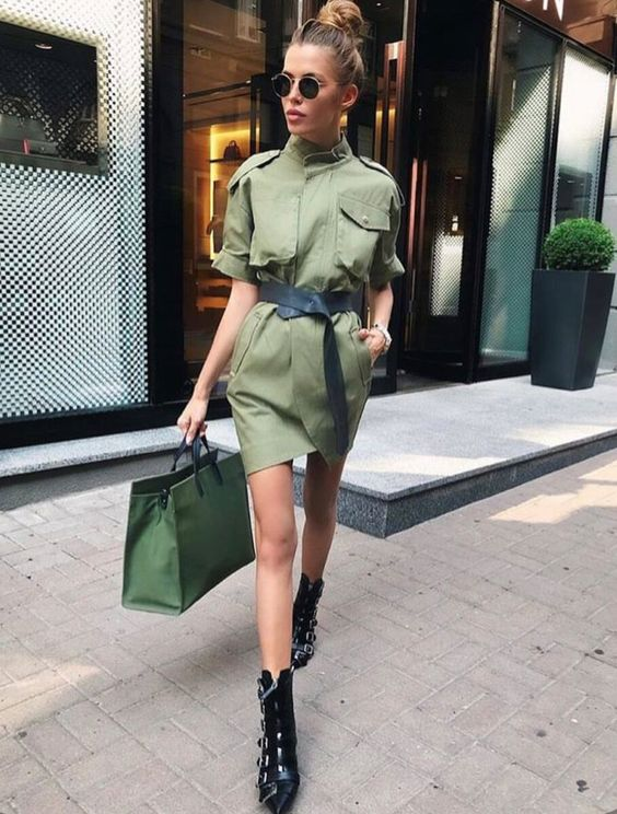 a long green safari jacket worn as a mini dress, with a black leather belt, black boots and a green tote