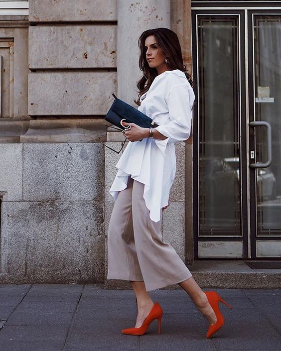 a long white shirt with a belt, light grey culottes, red heels, a black clutch and chic accessories